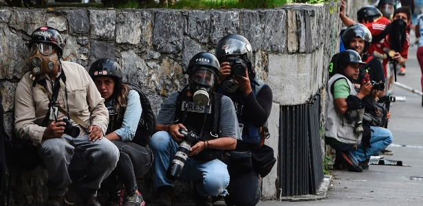 Jornalistas se protegem durante confrontos em Caracas, capital venezuelana - Juan Barreto/ AFP