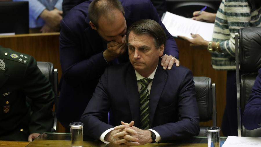 15.jul.2019 - Deputado federal Eduardo Bolsonaro (PSL-SP) sussurra no ouvido do pai, o presidente Jair Bolsonaro (PSL), durante sessão solene na Câmara - GABRIELA BILó/ESTADÃO CONTEÚDO
