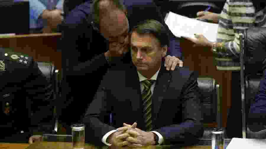 15.jul.2019 - Deputado federal Eduardo Bolsonaro (PSL-SP) sussurra no ouvido do pai, o presidente Jair Bolsonaro (PSL), durante sessão solene na Câmara - Gabriela Biló/ Estadão Conteúdo