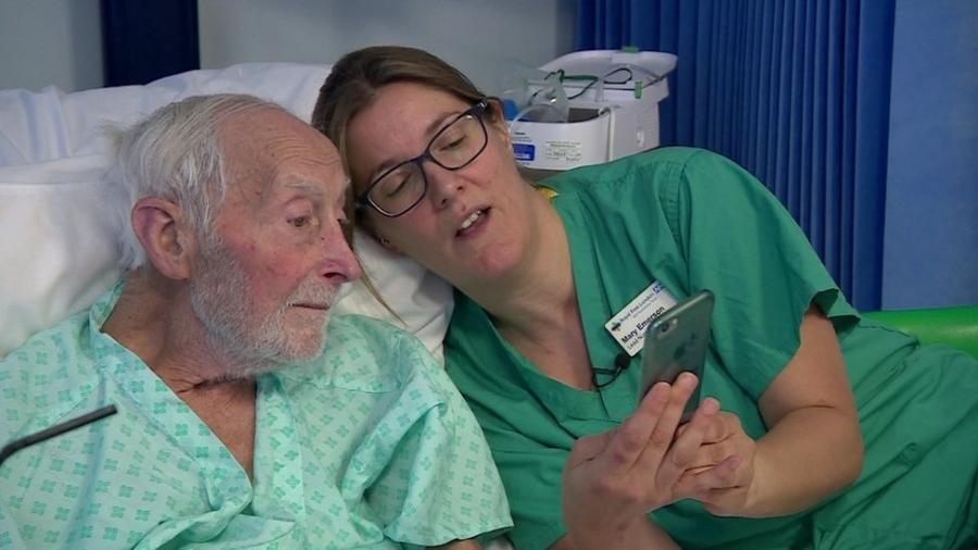 Enfermeira mostra a um paciente com lesão renal aguda os resultados de exames de sangue em seu celular - BBC