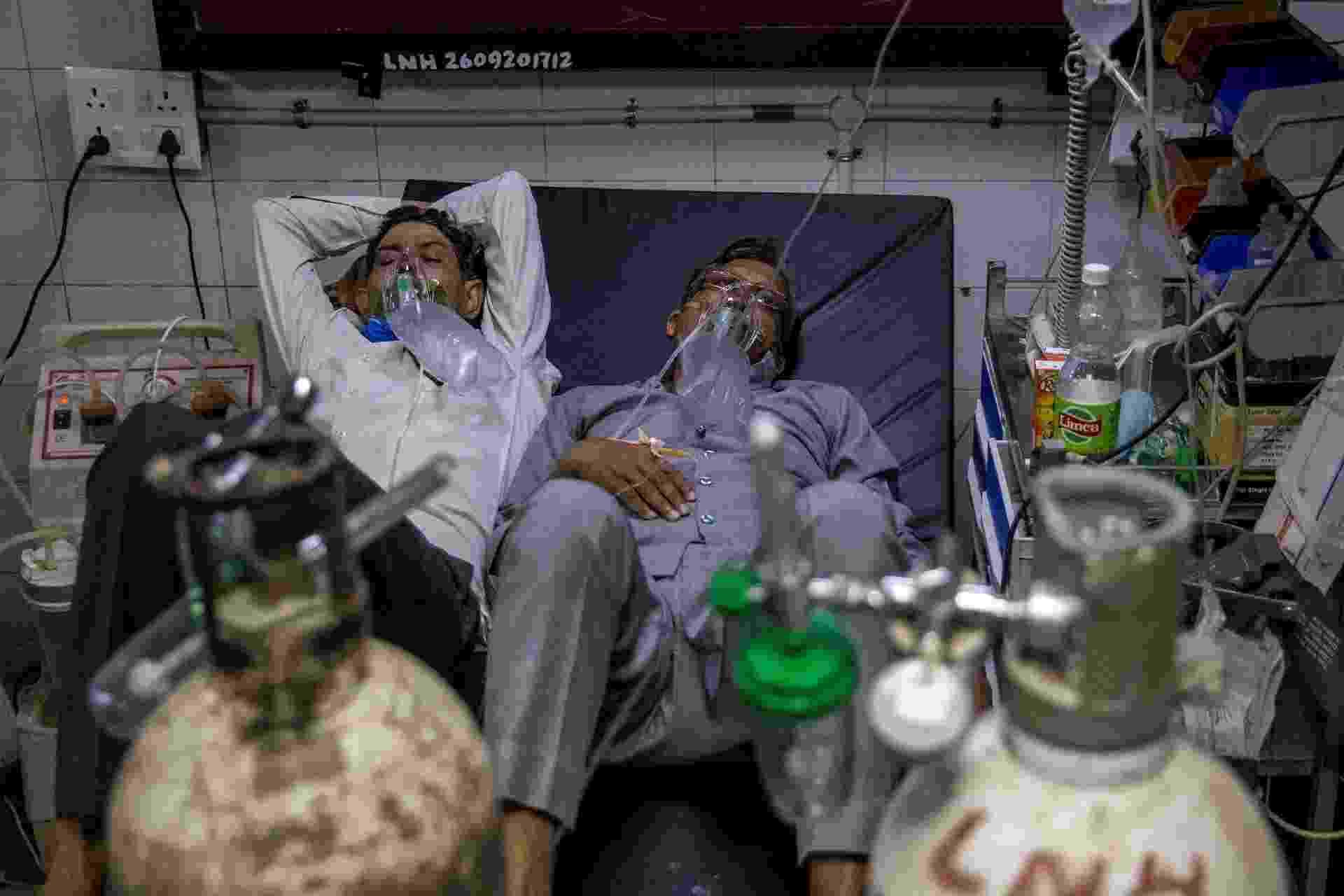 15.abr.2021 - Com número recorde de casos diários e leitos lotados, pacientes com covid-19 dividem a cama em hospital da Índia - DANISH SIDDIQUI/REUTERS