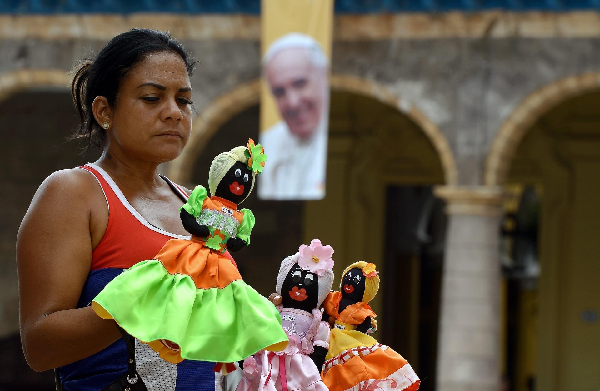 17.set.2015 - Vendedora ambulante comercializa bonecas próxima a um pôster com a imagem do papa Francico na praça da Catedral de Havana, em Cuba. O papa Francisco começará no próximo sábado (19) sua 10ª viagem internacional, um périplo que o levará a Cuba e aos Estados Unidos durante nove dias, nos quais fará 26 discursos