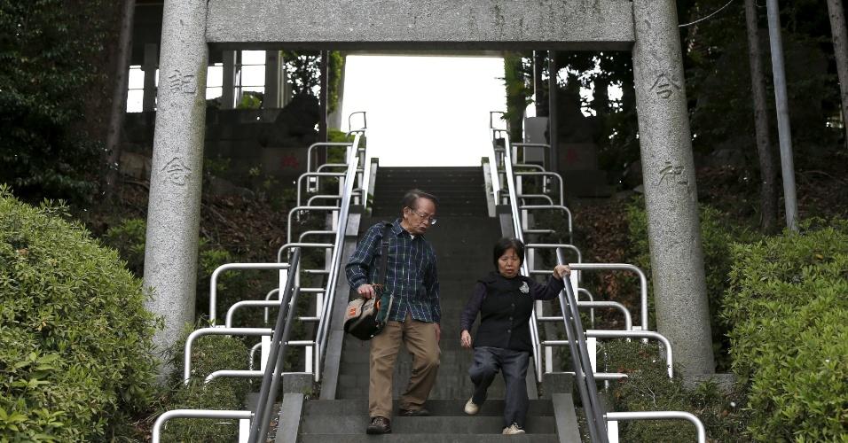 """18.abr.2016 - """"Eu planejava trabalhar até os 85 anos. Agora eu penso, será que vou passar o resto da minha vida cuidando da minha mulher??, se pergunta Kanemasa Ito. Na imagem, ele e Kimiko descem escada em direção ao mercado em Kawasaki, no sul de Tóquio (Japão). Há 11 anos eles descobriram que ela sofria de demência"""