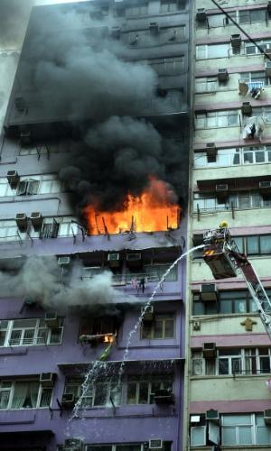 19.abr.2016 - Bombeiros trabalham para conter incêndio em edifício localizado em uma das principais vias de Hong Kong. Ao menos duas pessoas foram hospitalizadas por causa do incêndio, de acordo com a mídia local