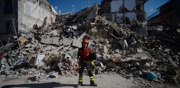 25.ago.2016 - Bombeiro diante de destroços em rua central de Amatrice, Itália