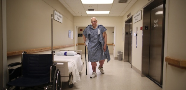 Paul Mason caminha em centro médico em Worcester, EUA, para tratar de uma infecção na perna