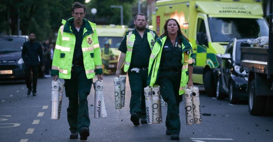 14.jun.2017 - Paramédicos chegam com oxigênio para atendimento dos moradores que conseguiram escapar do prédio em chamas