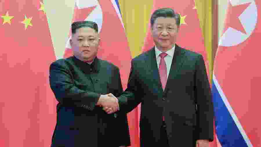 10.jan.2019 - Líder da Coreia do Norte, Kim Jong-un, aperta a mão do presidente chinês, Xi Jinping, durante visita à China - KCNA via KNS/AFP