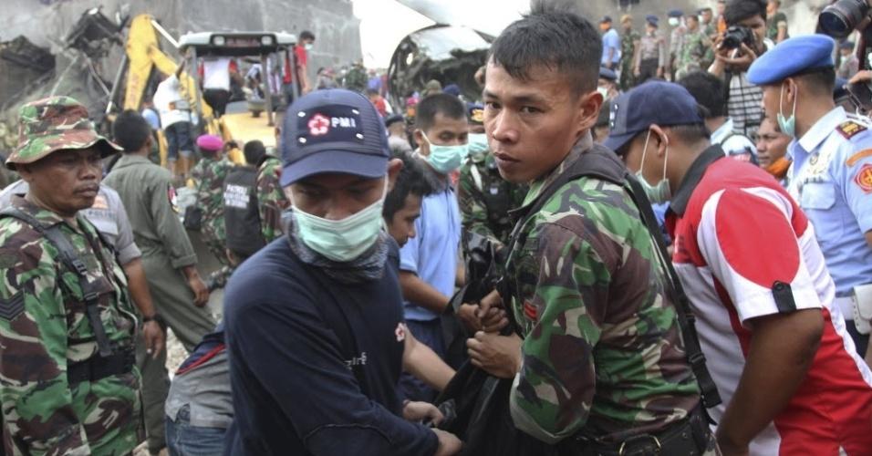 30.jun.2015 - Oficiais removem corpo de vítima do acidente com o avião de transporte militar indonésio C-130 Hercules, em área residencial da cidade de Medan, na ilha de Sumatra, Indonésia. O acidente incendiou casas e veículos e matou mais de cem pessoas