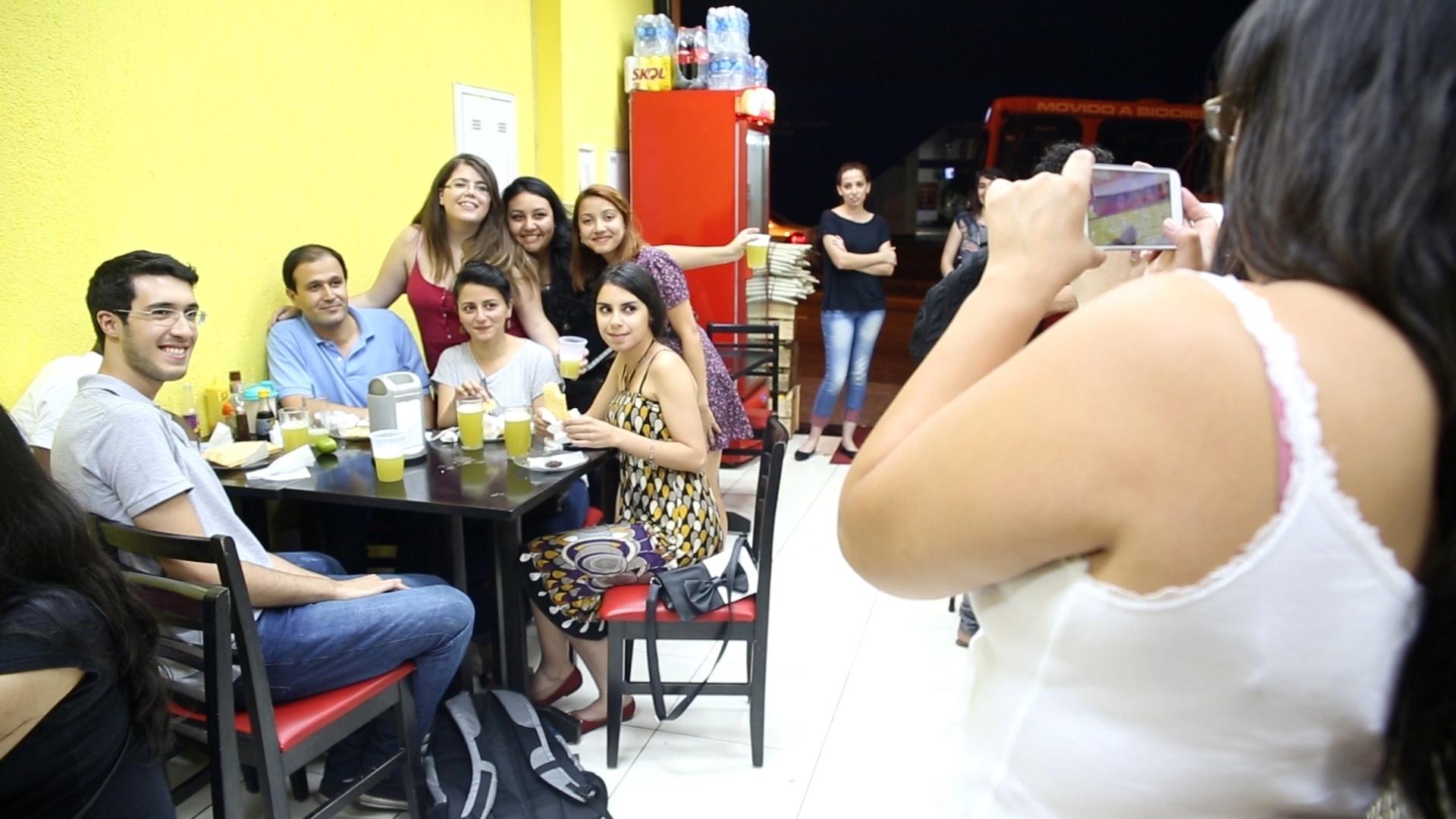 Refugiados alunos do curso de português do Memoref, da Unifesp, comem pastel e caldo de cana em bar de Guarulhos, na Grande São Paulo, durante atividade para conhecer a cultura brasileira. Foi a primeira vez em que eles provaram o clássico das feiras paulistanas