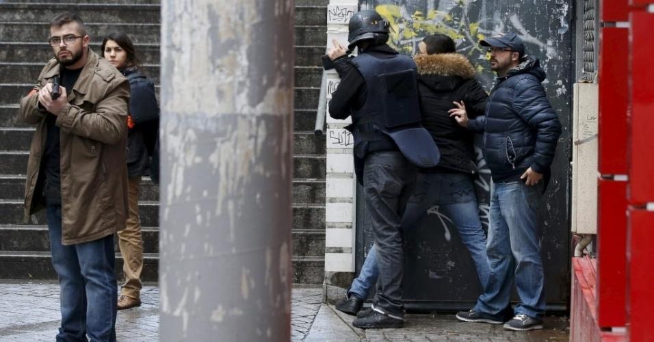 7.jan.2016 - Policiais franceses revistam um pedestre enquanto patrulham área após um homem ser morto próximo a delegacia do 18º distrito, em Paris (França). Policiais atiraram em um homem armado com uma faca, que tentava entrar na delegacia. O incidente aconteceu no dia em que se lembra o um ano do massacre liderado pelo Estado Islâmico na revista satírica Charlie Hebdo