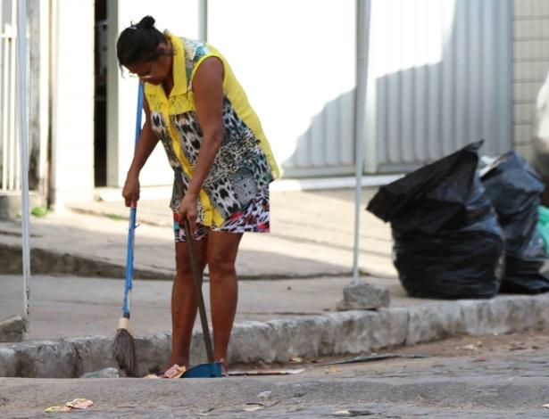 3.out.2016 - Mulher retira santinhos espalhados por rua do Recife, na manhã desta segunda-feira (3), um dia após o 1º turno das eleições municipais