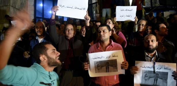 Jornalistas levantam cartazes em protesto contra a condenação de colegas