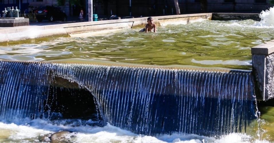 27.dez.2016 - Nada de passar vontade! Deu calor e o menino se jogou nas águas de um chafariz na praça da Sé, no centro de São Paulo