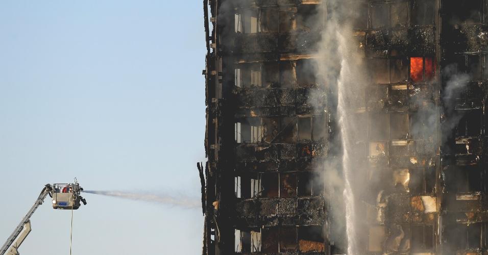 14.jun.2017 - Homens da Brigada de Incêndio de Londres trabalham no combate às chamas em prédio atingido desde o começo da madrugada