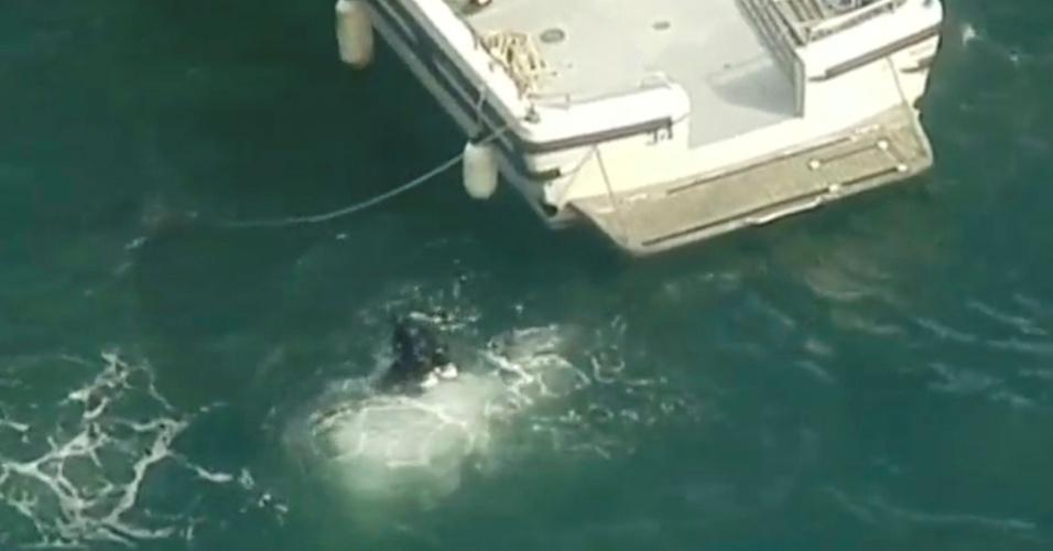 31.dez.2017 -- Mergulhador trabalha no resgate das vítimas de acidente com um hidroplano turístico em uma baía no norte da área metropolitana de Sydney, no sudeste da Austrália. Seis pessoas morreram