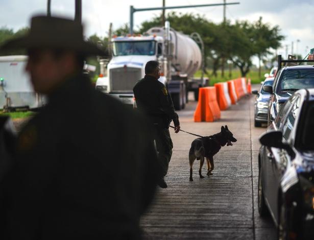 Um agente de patrulha de fronteira dos EUA confere carros que chegam no posto de controle em Falfurrias