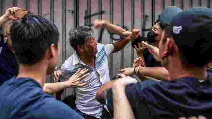 Homens brigam do lado de fora de shopping, em Hong Kong, durante protesto - Isaac Lawrence/AFP
