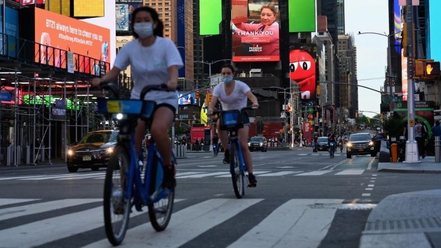 27/05/2020 - Ciclistas pedalam de máscara na Times Square, em Nova York, em meio à pandemia do novo coronavírus - Angela Weiss/AFP