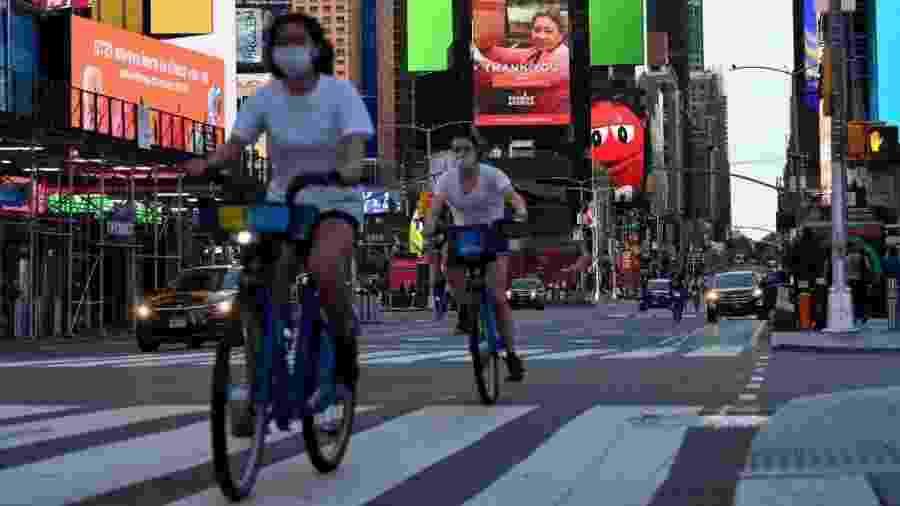 Ciclistas pedalam de máscara na Times Square. Cidade já foi epicentro da pandemia nos EUA - Angela Weiss/AFP