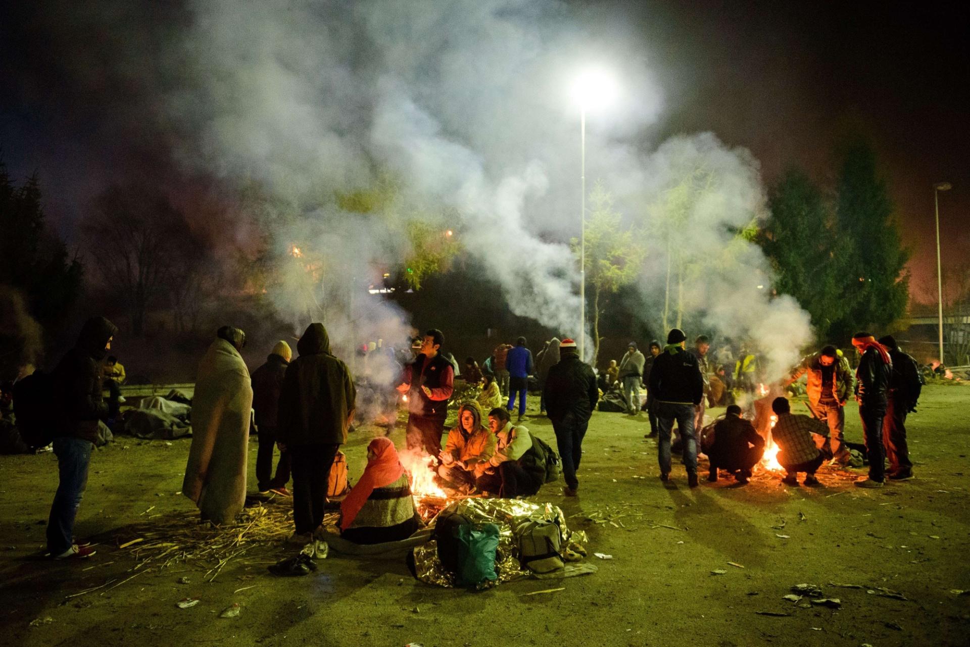 5.nov.2015 - Refugiados se sentam em volta de fogueiras enquanto esperam para cruzar fronteira eslovena-austríaca, em  Sentilj. Refugiados teriam feito 800 mil entradas ilegais na União Europeia este ano, disse o chefe da agência Frontex em uma entrevista ao jornal alemão Bild