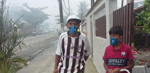 Geovan Rodrigues Brito, 48, e seu filho na área atingida pela nuvem tóxica no Guarujá. A filha de 4 dias já está na casa da avó