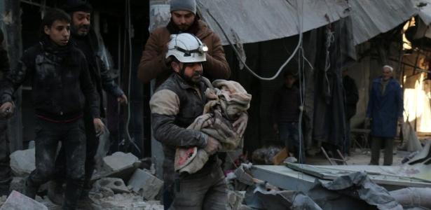Membro da Defesa Civil caminha sobre escombros enquanto carrega criança envolta em um cobertor, em Aleppo, na Síria