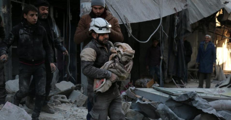 16.jan.2016 - Membro da Defesa Civil síria caminha sobre escombros enquanto carrega criança envolta em um cobertor, em Aleppo, na Síria