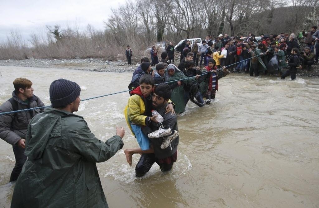 14.mar.2016 - Refugiados atravessam um rio com ajuda de uma corda na fronteira entre a Grécia e a Macedônia. A Grécia já soma cerca de 44 mil pessoas nos diferentes acampamentos distribuídos por todo seu território, segundo os dados divulgados nesta segunda-feira (14) pelo centro de coordenação do governo