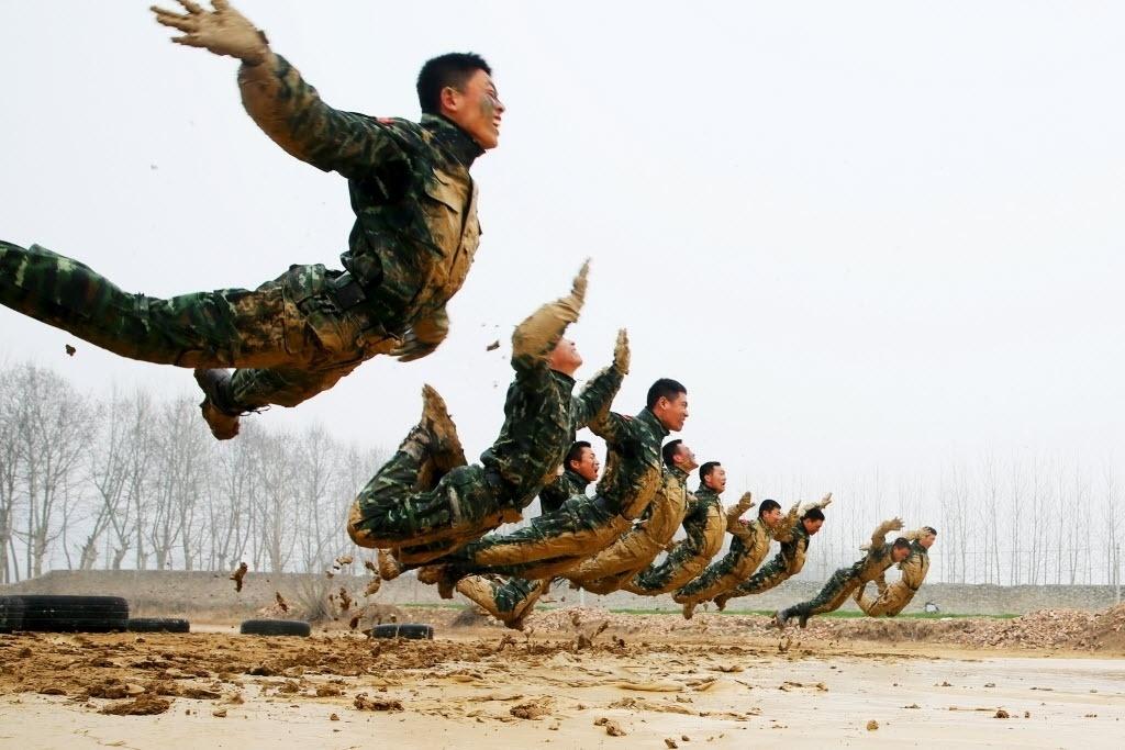 17.mar.2016 - Um grupo de policiais especiais treina na lama em Suzhou, na China