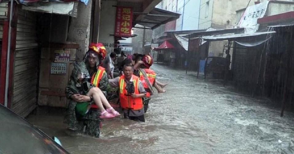 19.jun.2016 - Socorristas resgatam crianças ilhadas em Dawu County, em Hubei (China), após a passagem de chuvas torrenciais que provocaram estragos na região. A catástrofe deixou ao menos 12 desaparecidos e 400 mil desabrigados