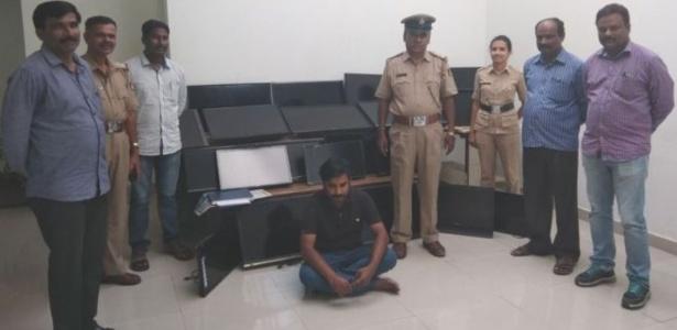 O homem, sentado ao centro, foi preso acusado de ter furtado mais de 120 TVs de hotéis no sul da Índia, nos últimos quatro meses
