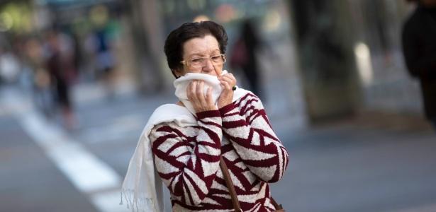 Mulher caminha em meio ao frio que voltou à SP na manhã de domingo (20) na Paulista