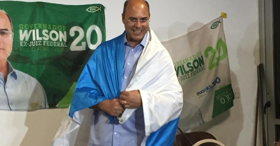 Wilson Witzel envolto em bandeira do Estado do Rio