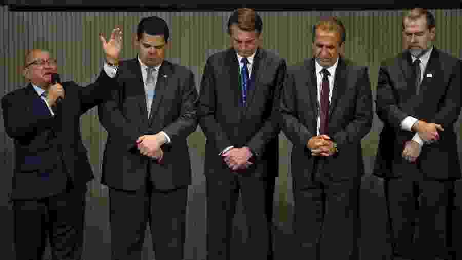 Um pastor evangélico prega ao lado de Bolsonaro, o presidente do senado, Davi Alcolumbre, o pastor Silas Malafaia e o presidente do STF, Dias Toffoli - Mauro Pimentel/AFP