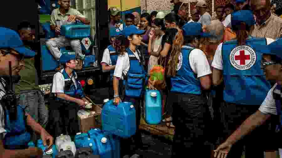 Trabalhadores da Cruz Vermelha distribuem água potável em Catia, um bairro operário de Caracas, na Venezuela - Meridith Kohut/The New York Times