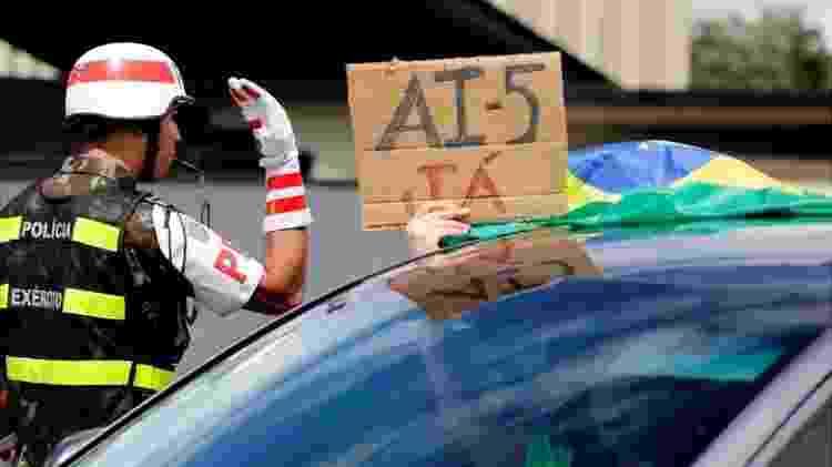 Manifestante pedindo volta do AI-5 em protesto em Brasília no domingo (20); PGR pediu inquérito para apurar protestos - AFP - AFP