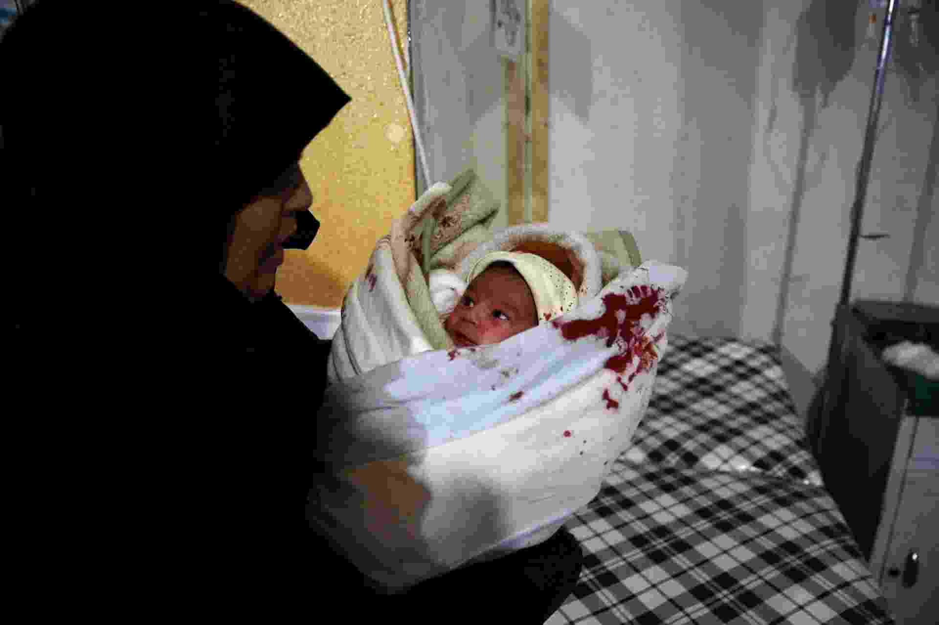 Segundo ativistas, o bombardeiro mais recente contra instalações hospitalares foi realizado pelas forças de Assad no último dia 13 de dezembro. Muitos pacientes ficaram feridos na ação. Na foto, uma das mulheres que trabalham no local socorre um dos bebês que estava no bercário - Bassam Khabieh/Reuters