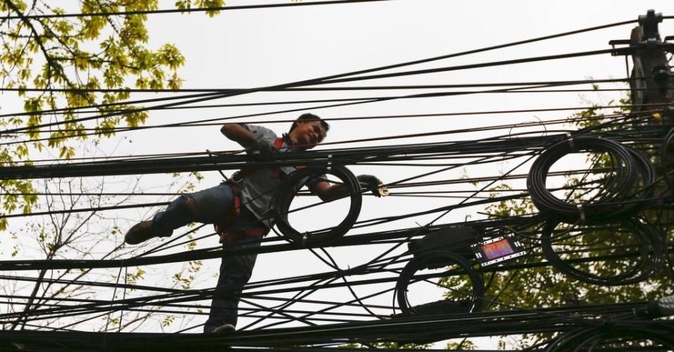 2.fev.2016 - Funcionário faz manutenção da rede elétrica em Bancoc, Tailândia, se pendurando nos fios