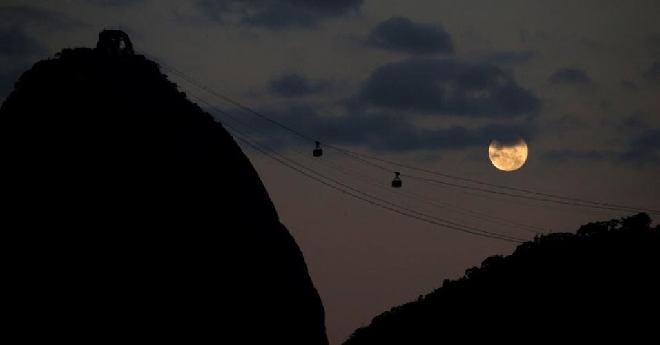 20.mai.2016 - Teleféricos cruzam o Pão de Açúcar em frente à lua cheia, no Rio de Janeiro
