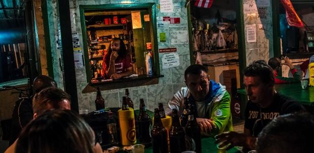 Araújo (ao fundo) recebe clientes no Bar do Bin Laden, no Rio de Janeiro