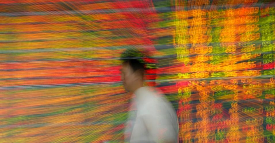 11.nov.2016 - Homem passa por painel eletrônico de ações em Bangkok (Tailândia)