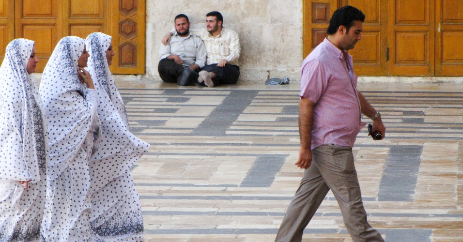 Homem e suas três mulheres caminham no pátio central da Mesquita Umayyad, construída no século 8 e parcialmente destruída pela guerra entre o regime de Assad e os rebeldes