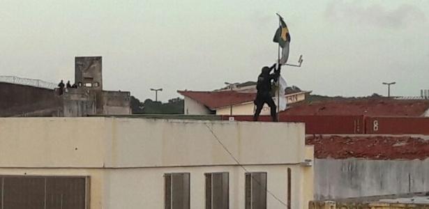 Agente hasteia bandeira do Brasil no telhado da penitenciária de Alcaçuz