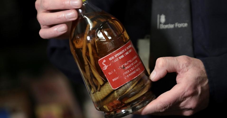 28.dez.2017 - Agente mostra garrafa com tônico misturado a cobras apreendido no aeroporto de Heathrow, em Londres