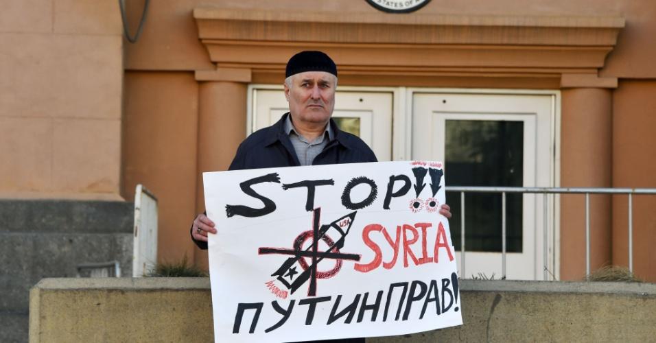 14.abr.2018 - Homem protesta com cartaz contra os ataques aéreos à Síria em frente a embaixada dos Estados Unidos em Moscou, neste sábado (14). A Rússia, aliada do regime da ditadura de Bashar Al Assad, convocou uma reunião de emergência no Conselho de Segurança da ONU