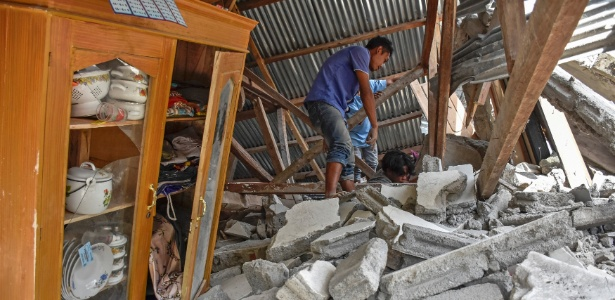 Homem caminha sobre escombros de uma casa durante busca por pertences dos turistas malaios que morreram no terremoto no vilarejo de Sembalun Selong, em Lombok, Indonesia - Ahmad Subaidi/Antara Foto/Reuters