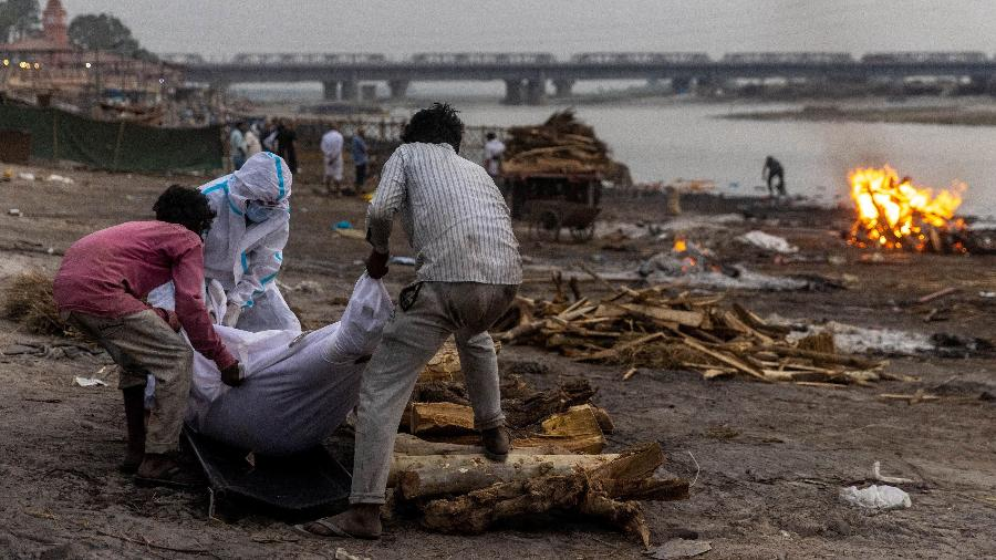 Pessoas colocam o corpo de um homem que morreu de covid-19, em uma pira antes de sua cremação nas margens do rio Ganges em Garhmukteshwar, no estado norte de Uttar Pradesh, Índia - Danish Siddiqui/Reuters