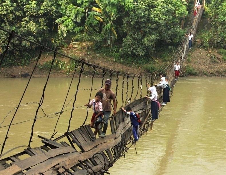 Indonésia - Para ir à escola, crianças atravessam o rio Ciberang por meio de uma ponte quebrada