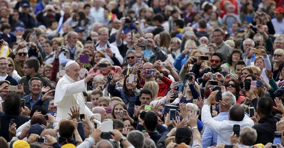30.set.2015 - Cercado por multidão e fotografado por boa parte dela, o papa Francisco acena aos fiéis ao chegar na praça São Pedro, no Vaticano. Depois de passar dias em Cuba e nos Estados Unidos, o pontífice voltou a celebrar uma audiência no local